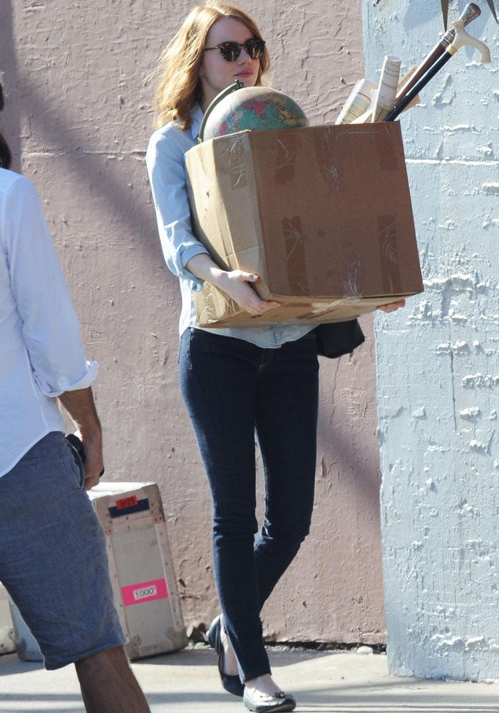 """Emma Stone wears sunglasses and carries a box of props on the set of """"La La Land"""""""