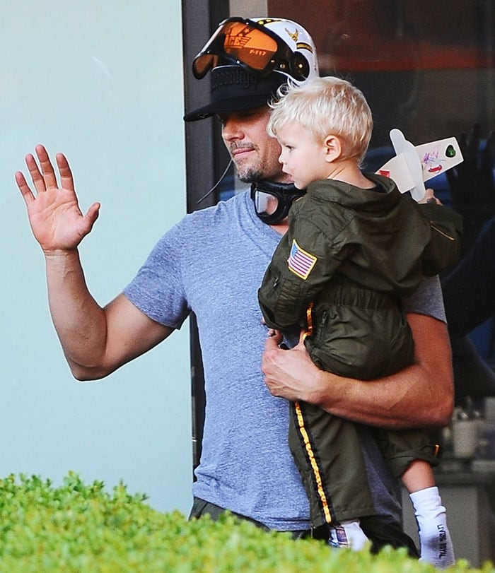 Fergie's husband, Josh Duhamel, hoists Axl on his hip and waves