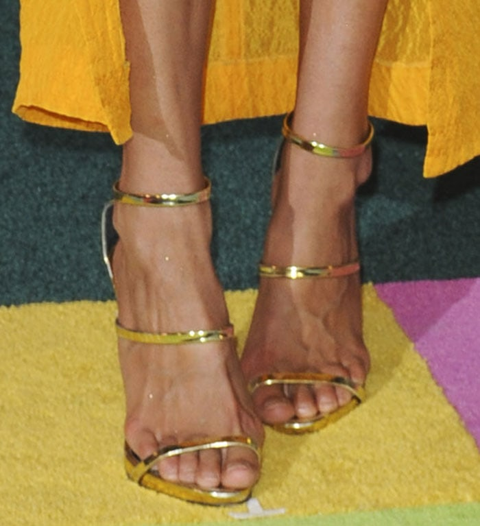 Gigi Hadid totters in a pair of triple-strap gold metallic sandals from Giuseppe Zanotti