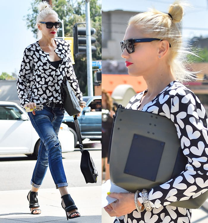 Gwen clutches her purse in one arm and cellphone in the other as she struts in a pair of black heels from her own line