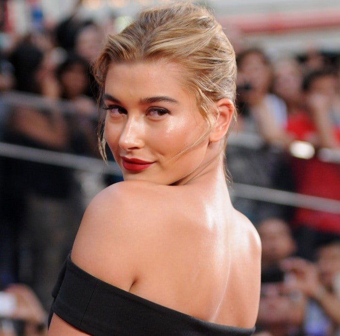"Hailey Baldwin shows off her off-the-shoulder mini ""Kristelle"" dress by Elizabeth and James at the ""Mission Impossible - Rogue Nation"" New York Premiere at Duffy Square in Times Square on July 27, 2015, in New York City"