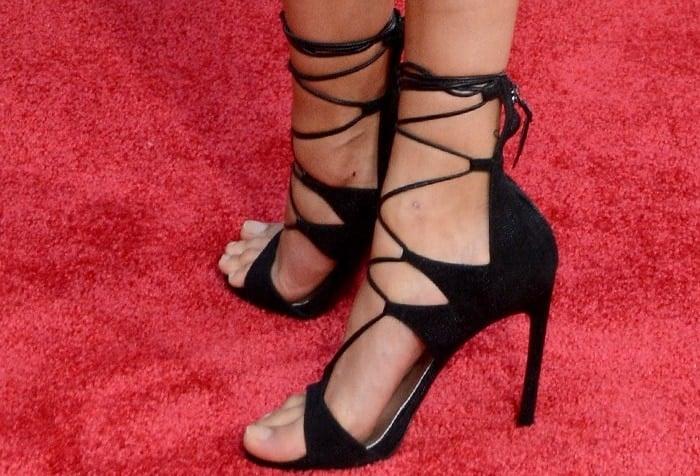 Hailey Baldwin shows off her feet in black strappy Stuart Weitzman sandals