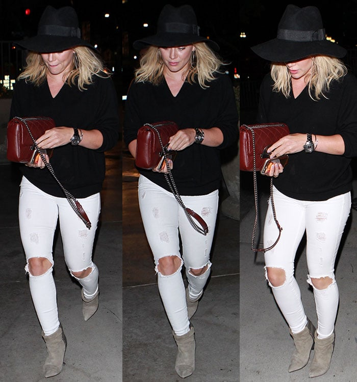 Hilary Duff's blonde tresses peek out from beneath her black hat