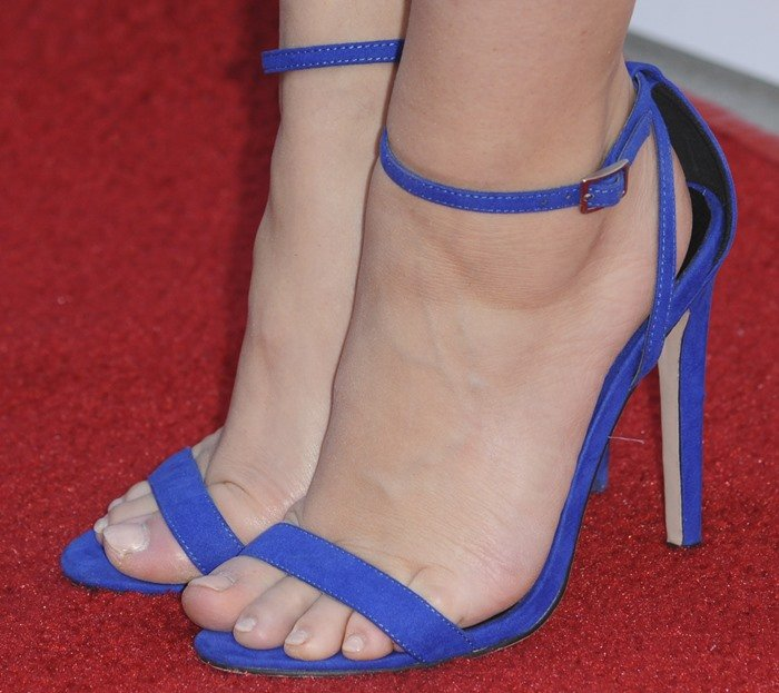 Holland Roden's sexy feet in cobalt blue sandals that contrast with the movie premiere's red carpet