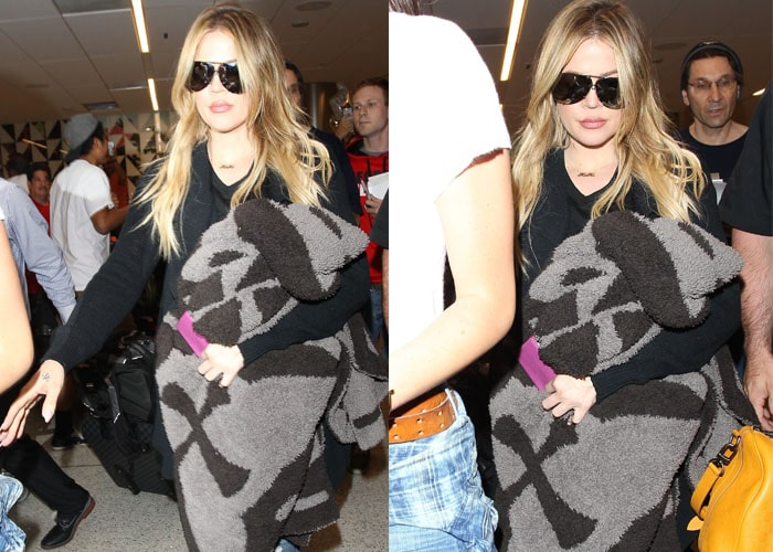 Khloe hides her eyes behind aviators and holds what appears to be a large blanket as she strolls through LAX