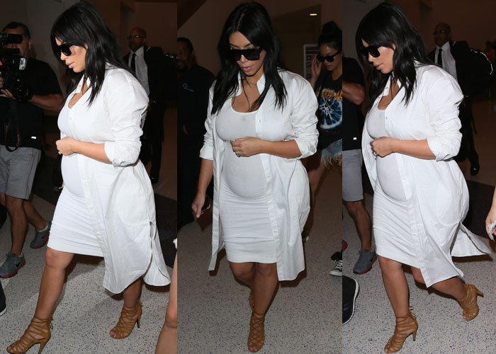 Kim wore a tight white dress around her growing pregnancy bump, which she wore under a white knee-length button-down