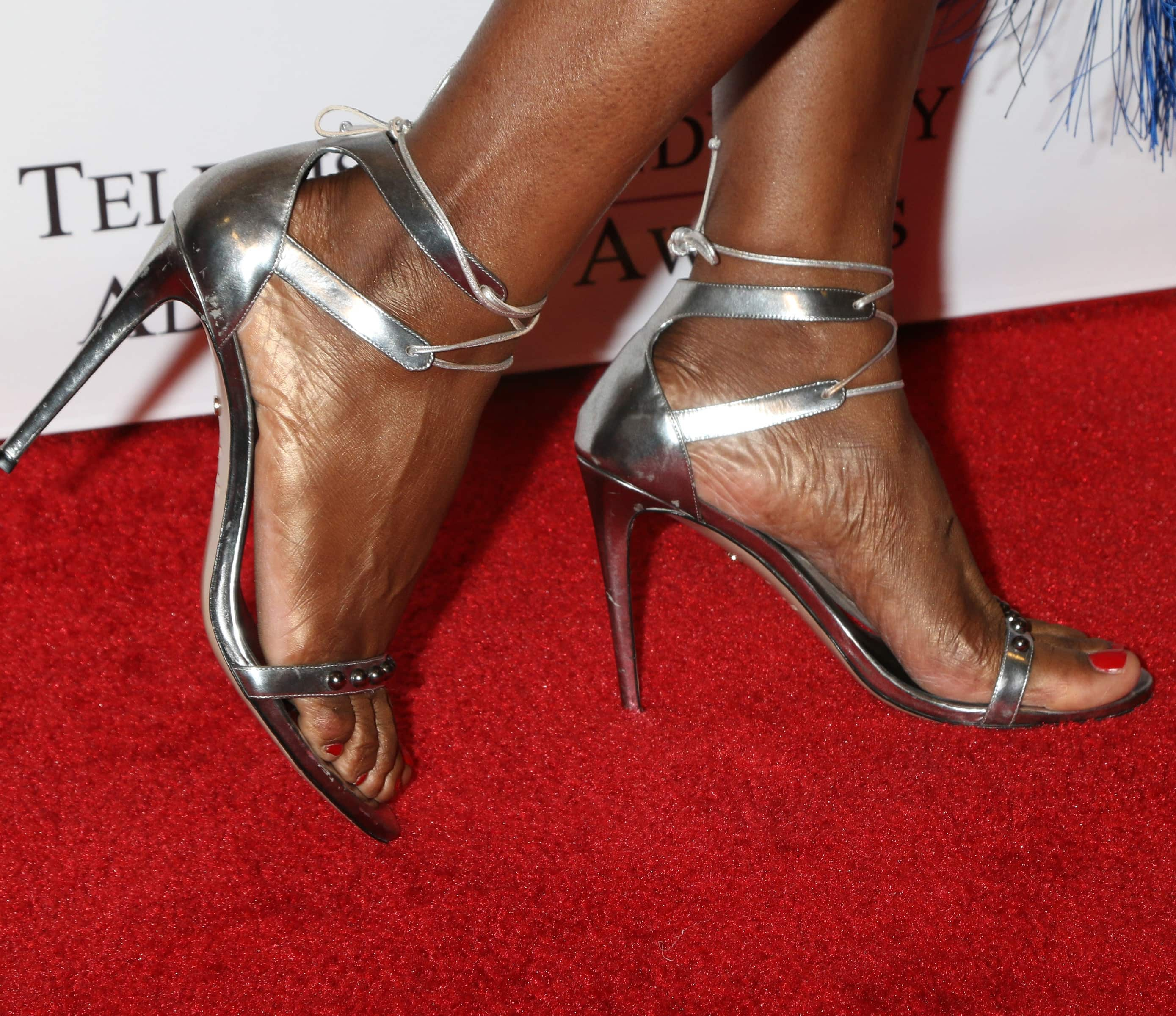 Laverne Cox's enormous feet in metallic ankle-strap sandals