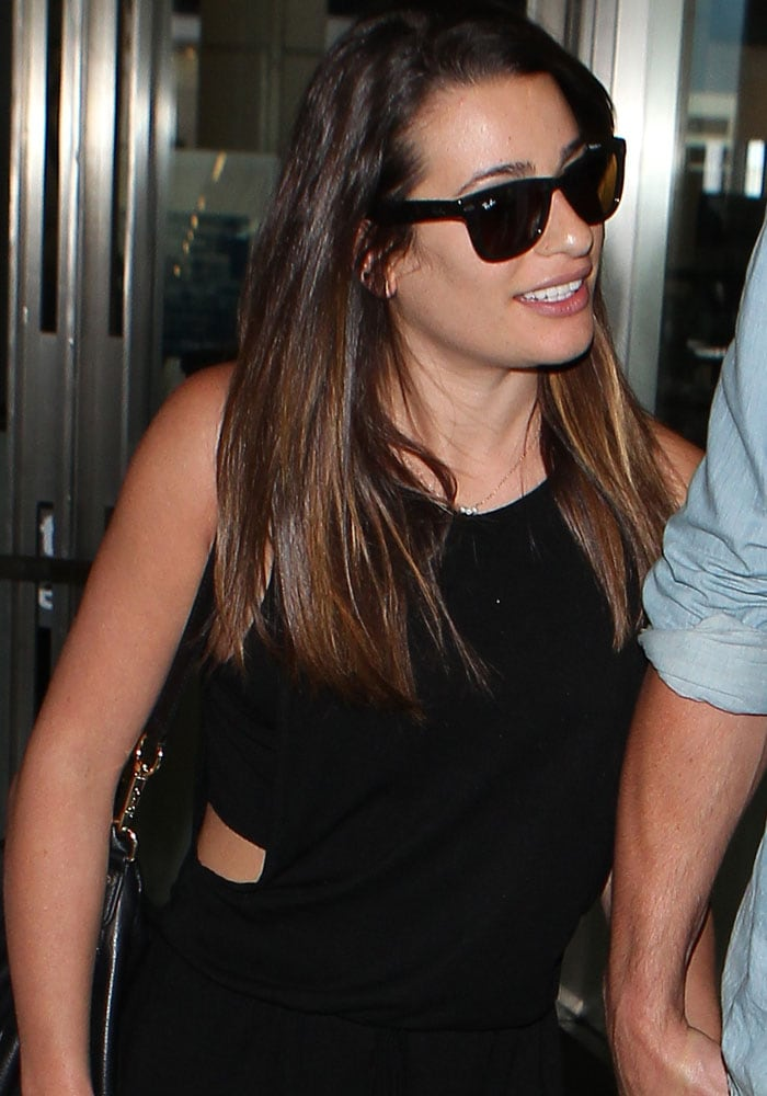 A camera shy Lea Michele arrives at Los Angeles International Airport