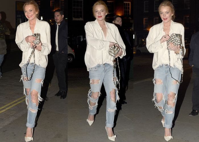 Lindsey Lohan smiles and clutches her handbag as she arrives for dinner at the popular London hangout