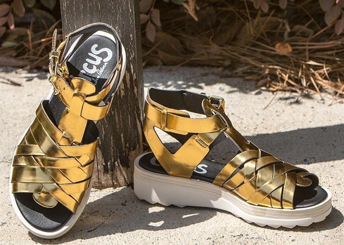 Woven metallic straps add eye-catching glamour to a look-defining sandal set on a sleek platform wedge