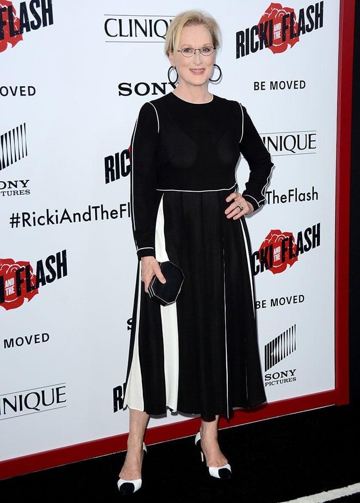 Meryl Streep accessorized with black hoop earrings and a black clutch