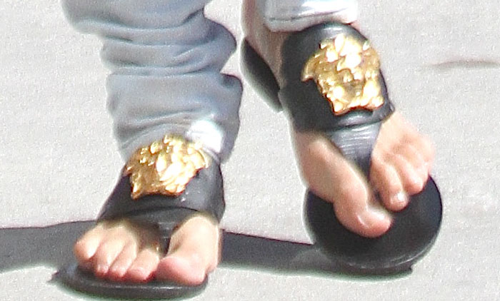 Michelle Rodriguez lets the hem of her white pants slouch around the tops of her Versace sandals.