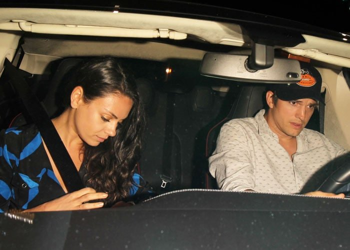 Mila Kunis lets her long dark hair fall over her shoulder and in front of her chevron-printed dress as she sits in a car with husband Ashton Kutcher