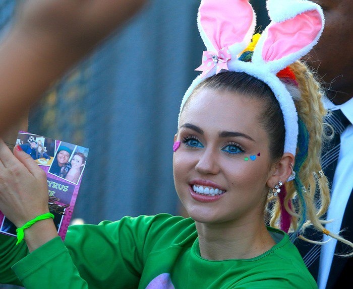 Miley Cyrus shows off her bunny ears, electric blue eyeliner, face stickers and earrings as she leaves ABC Studios in Los Angeles