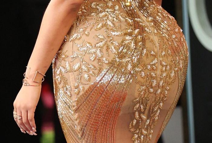 Nicki Minaj flaunts her infamous backside in a shimmering gold embellished dress