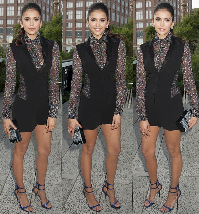 Nina Dobrev accessorized with a pair of floral earrings and a statement ring and carried a glittery Edie Parker box clutch