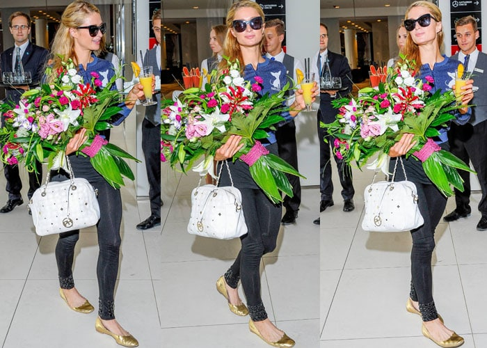 Paris Hilton juggles flowers, a fruity drink and a white tote bag as she arrives in Poland
