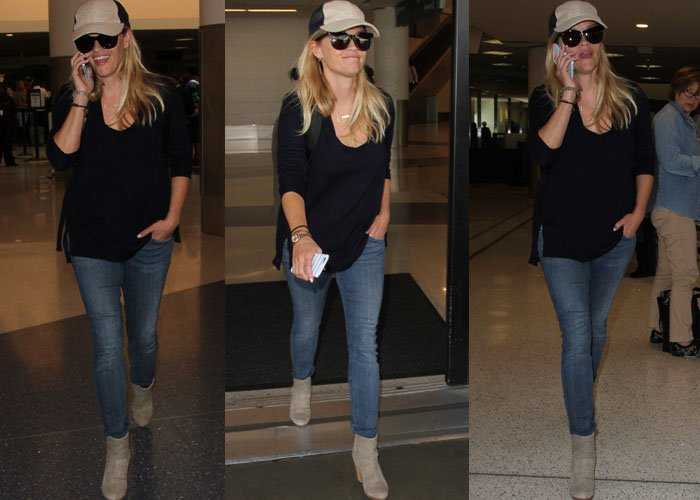 Reese Witherspoon chats on her phone and smiles at waiting paparazzi as she strolls through LAX