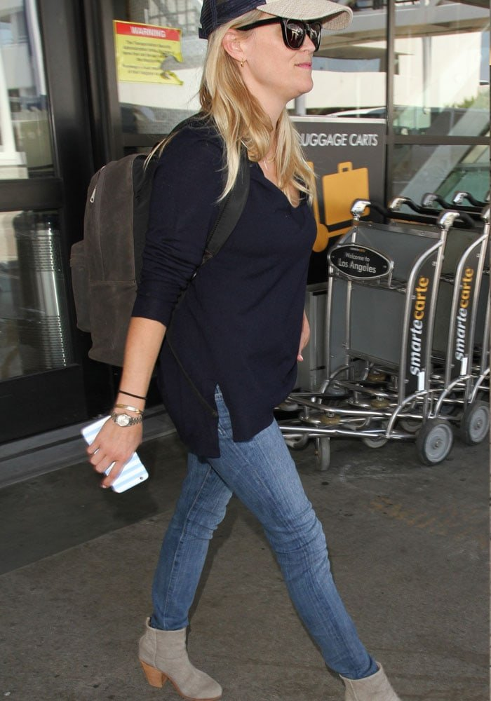 Reese Witherspoon grasps her cellphone as she exits the airport