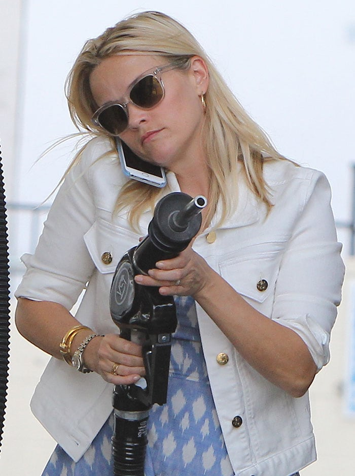 Reese Witherspoon pumps gas with her blonde hair worn down