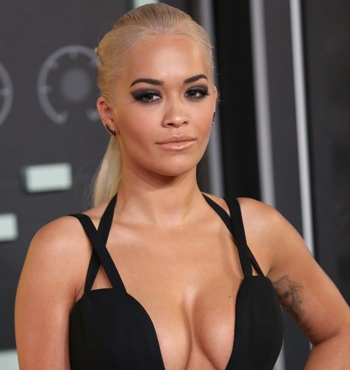 Rita Ora's inner-arm tattoo peeks out as she poses in a black Vera Wang dress