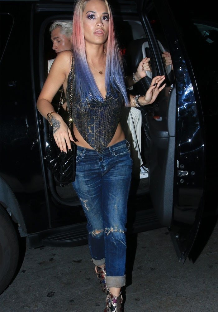 Rita Ora shows off black nails and a hand/ wrist tattoo as she steps out of a vehicle on her way to the club