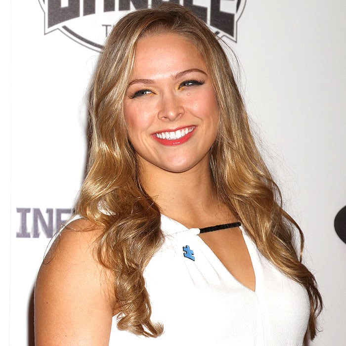 Ronda Rousey showing her puzzle piece pin and bronze inner-eye makeup