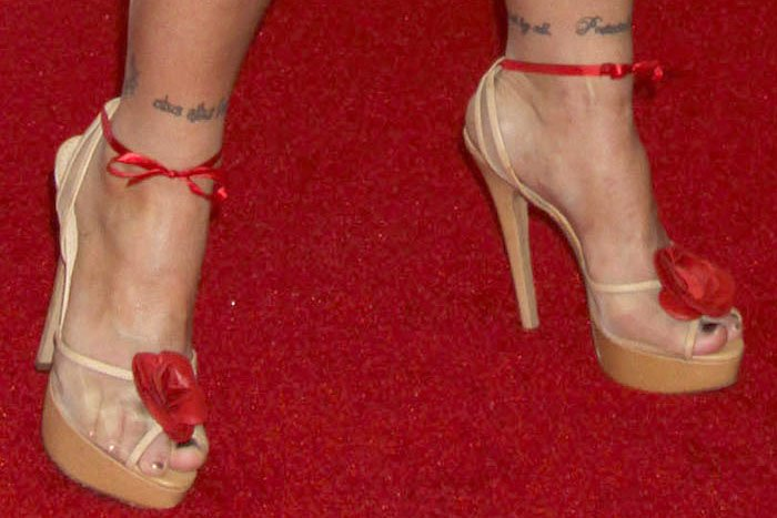 """Ronda Rousey wearing Charlotte Olympia """"Florentina"""" platform sandals with the ankle straps traded out for red ribbons"""