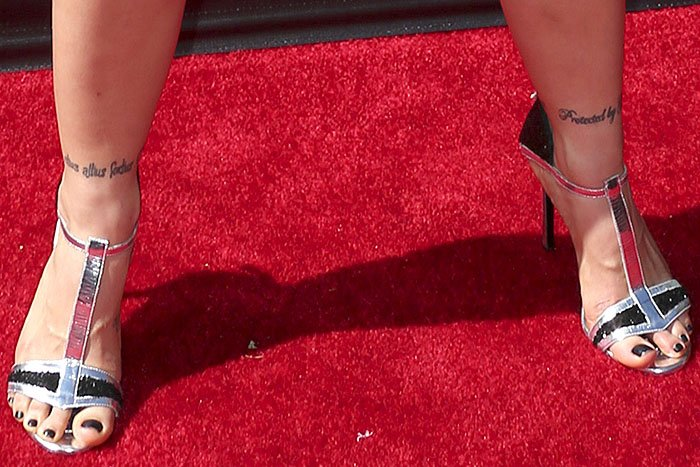 Ronda Rousey's strong legs-apart pose in silver t-strap sandals with glittery black trim