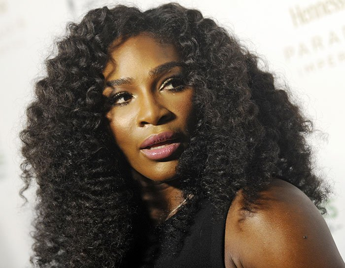 Serena Williams' voluminous curly hairstyle with an off-center parting