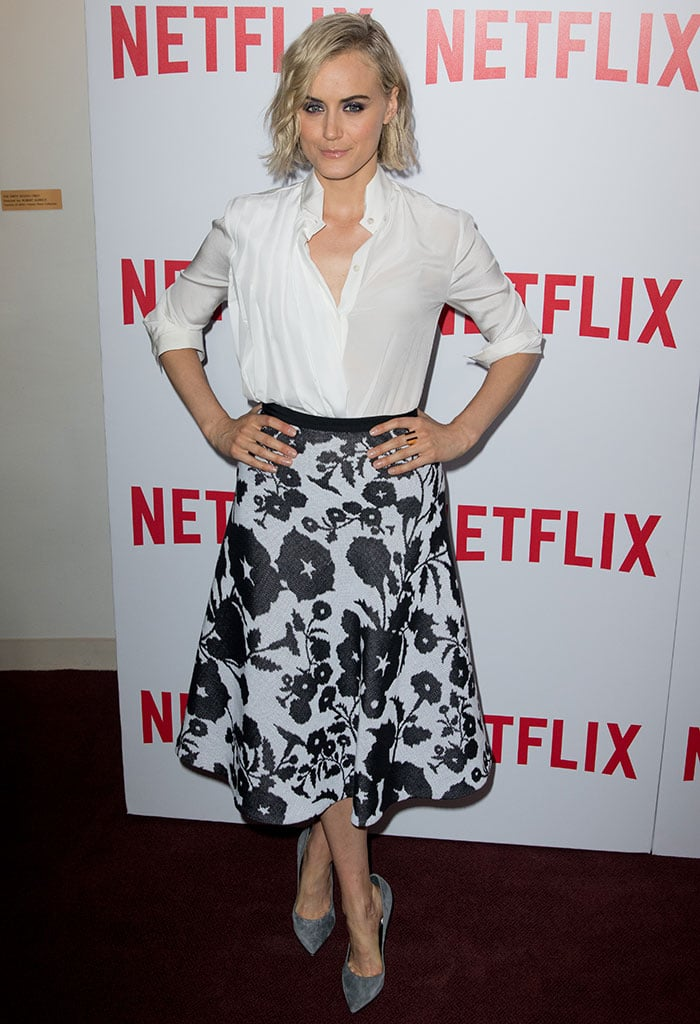 Taylor Schilling in a partially unbuttoned white shirt worn with an upturned collar and rolled-up sleeves