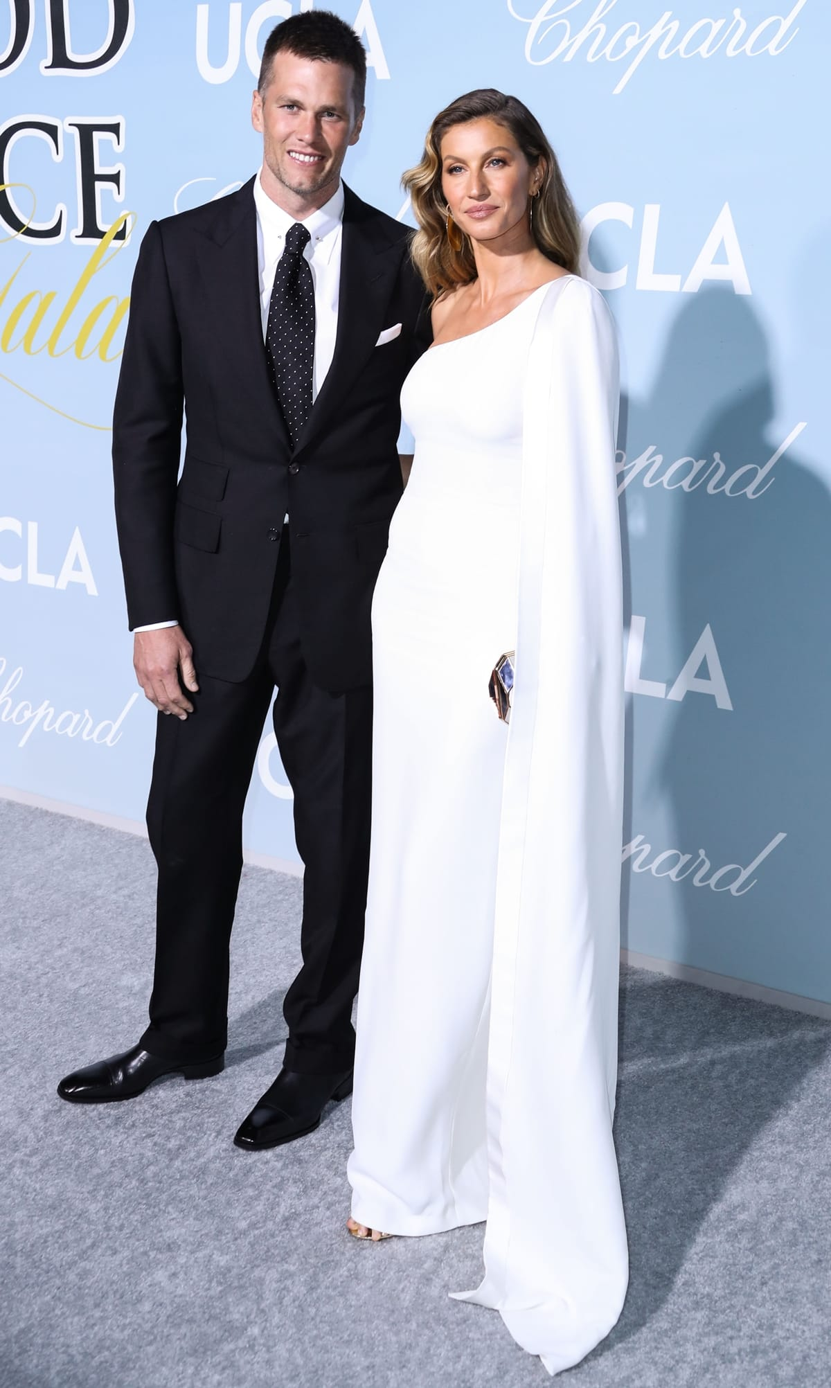 Gisele Bündchen in a white one-shoulder Stella McCartney dress with Tom Brady in a black suit at the 2019 Hollywood For Science Gala