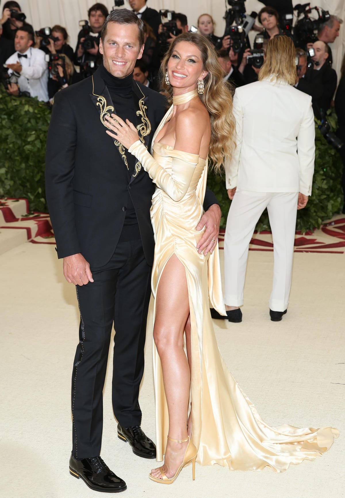 Gisele Bündchen in an eco-friendly long, gold Versace dress with Tom Brady in an embellished tuxedo at the 2018 Met Gala