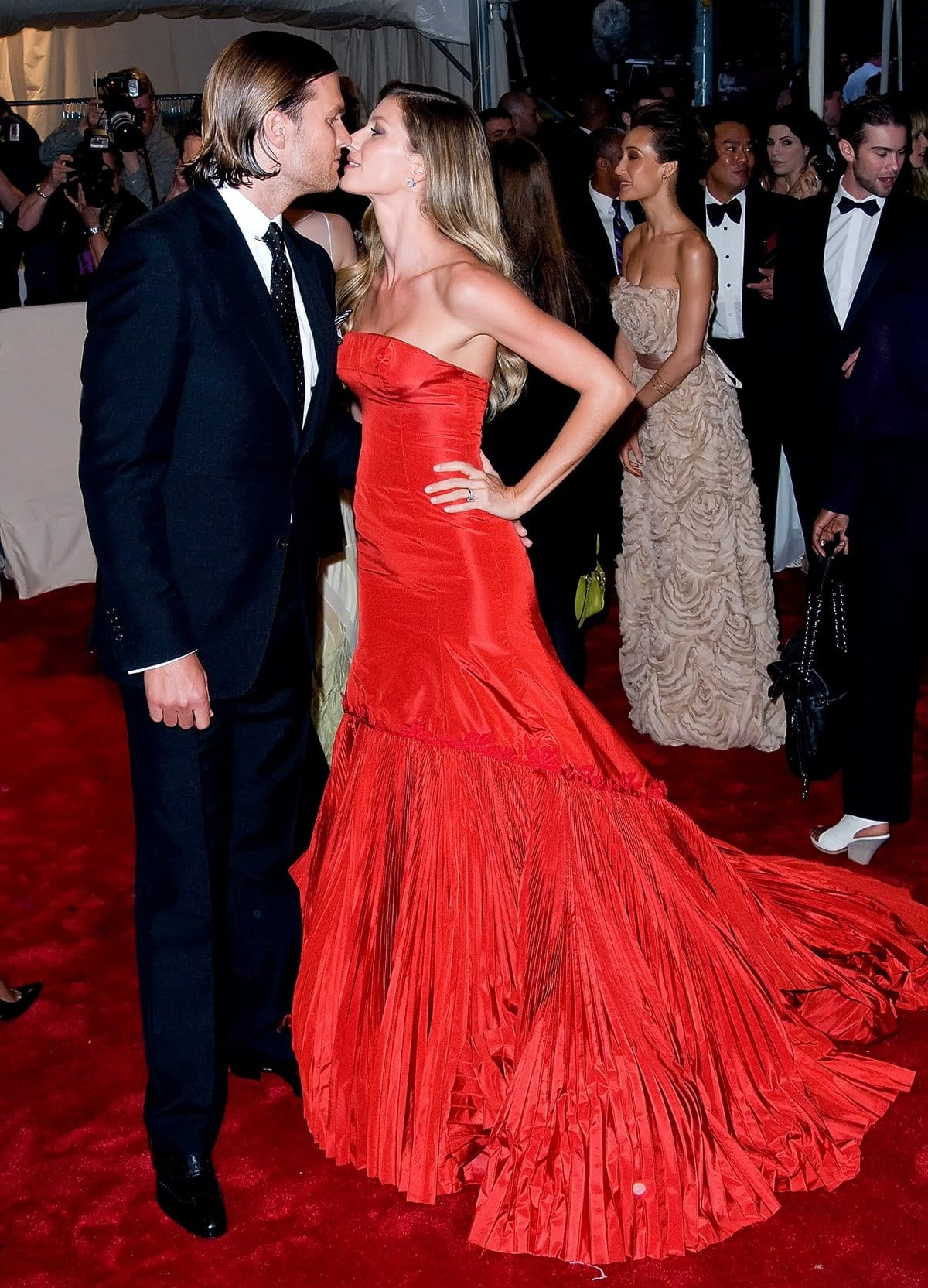 Gisele Bündchen in a red strapless Alexander McQueen Fall 2005 red fish-tail dress kissing Tom Brady at the 2011 Met Gala