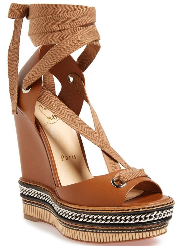 A chain-wrapped platform grounds a sleek Italian-leather wedge sandal
