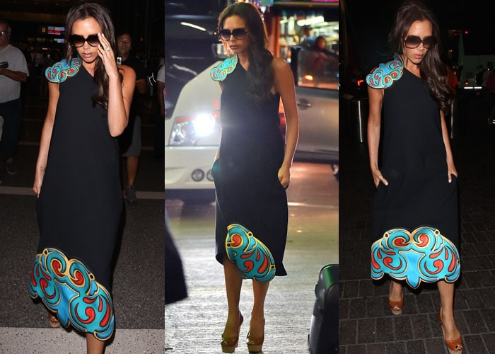 Victoria Beckham shows off the design of a dress from her own collection as she strolls through the Los Angeles airport