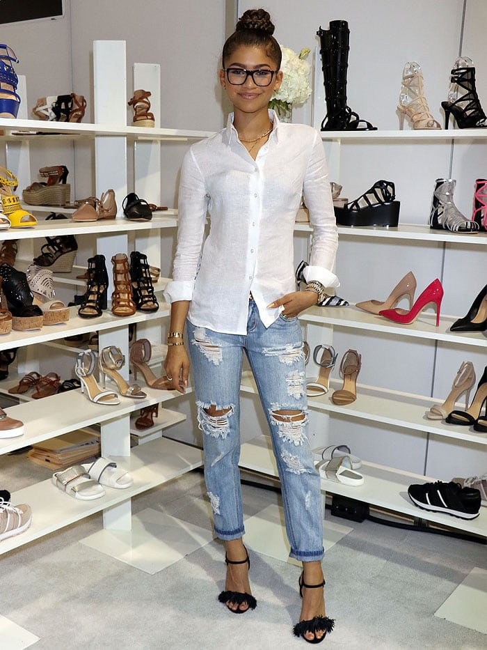 Zendaya posing in front of a wall of her Daya shoes displayed at FN Platform during the semi-annual MAGIC fashion trade show
