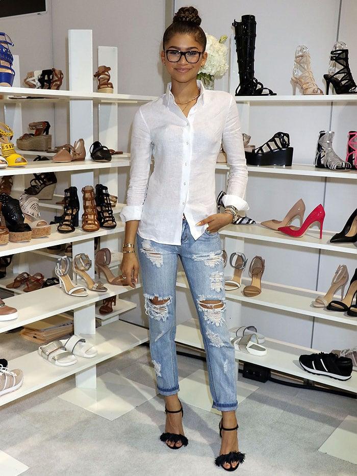 Zendaya posing in front of awall of her Daya shoesdisplayed at FN Platform duringthe semi-annualMAGIC fashiontrade show