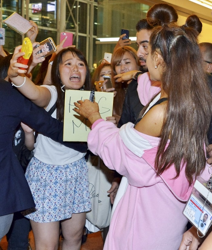 Ariana Grande greets fans at the Tokyo International Airport dressed in a pink unicorn onesie in Tokyo, Japan on August 13, 2015