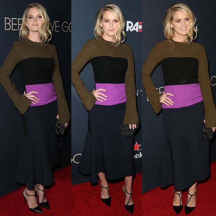 Alice Eve clutches an embellished black bag in one hand as she smiles for the cameras