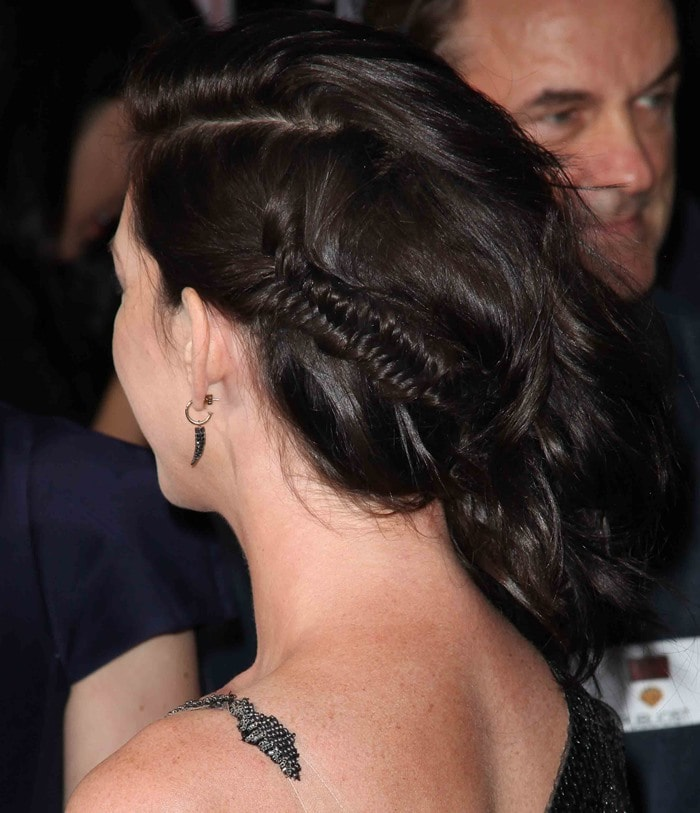Anne Hathaway sweeps her dark hair back into a side-swept style complete with a fishtail braid