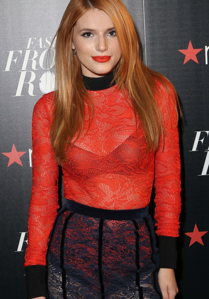 Bella Thorne wears a sheer red-and-black Balmain dress as she poses in front of a Macy's-branded backdrop