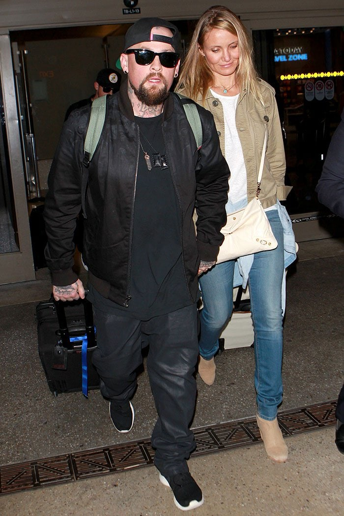 Benji Madden and Cameron Diaz holding hands as they make their way out of LAX Airport