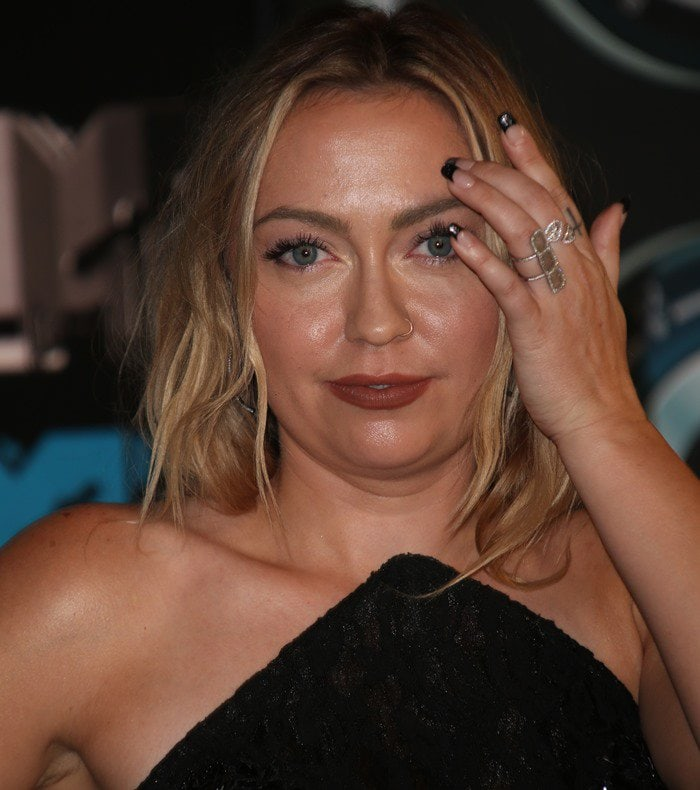 Brandi Cyrus brushes her messy blonde hair out of her face as she poses for a photo