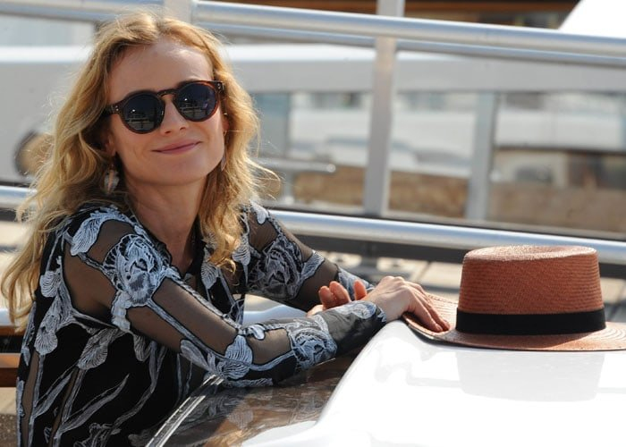 Diane Kruger shows off her Komono sunglasses and her Janessa Leone straw hat as she poses for photos
