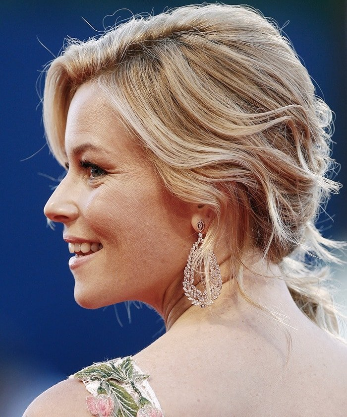 Elizabeth Banks turns her head to the side to flaunt her wavy blonde updo and shining silver earrings