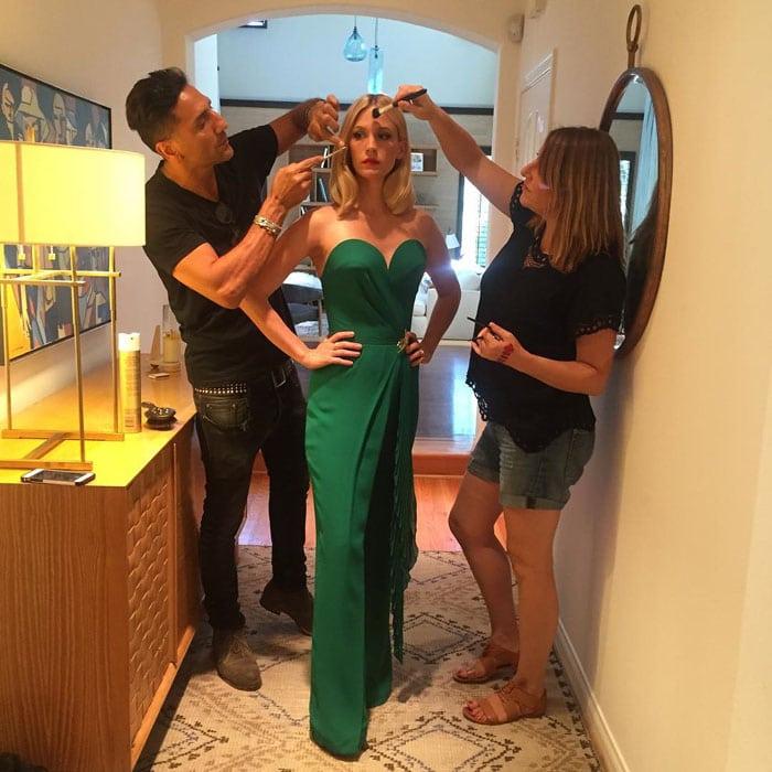 January Jones holds still with her hands on her hips as her makeup and hair is touched up for the Emmys