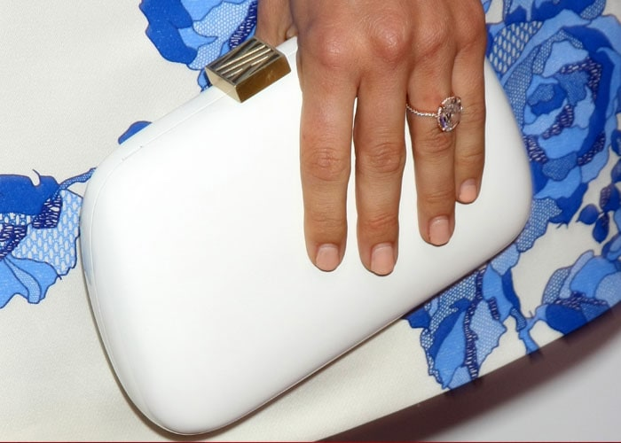 Julianne Hough toting a white clutch while revealing her engagement ring