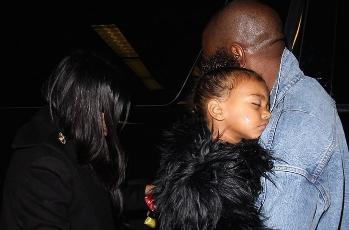 North West sleeps on the shoulder of Kanye West as her family enters the LAX airport