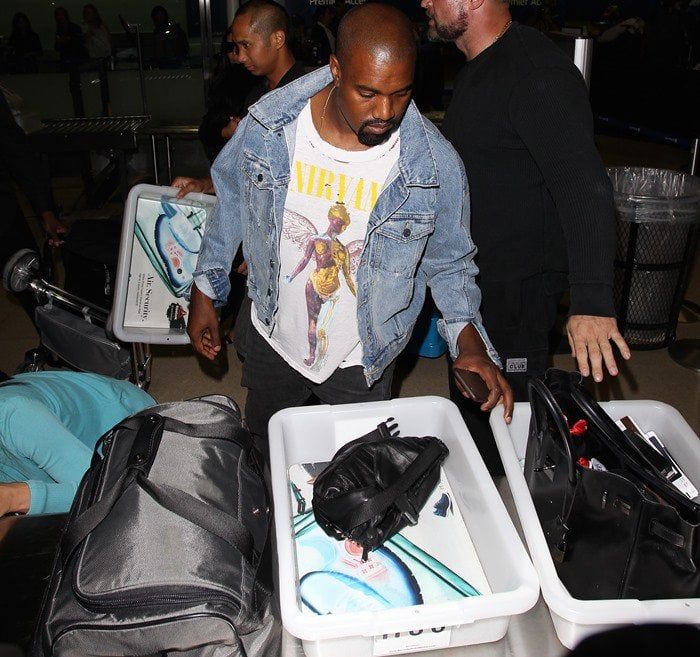 Kanye West goes through security at LAX in a denim jacket and printed white t-shirt